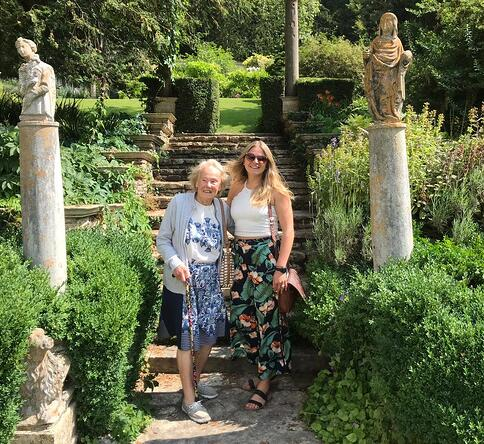 The author with her grandma stood together at the base of an ornate set of garden stairs
